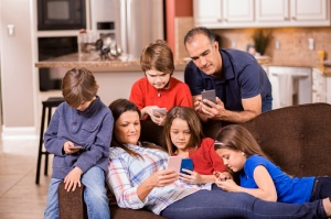 Family using cell phones at home. Children, parents. Technology.